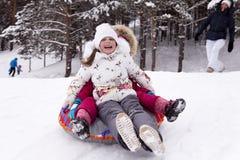 Счастливая маленькая девочка screams при наслаждение, свертывая с холмом снега Стоковая Фотография RF