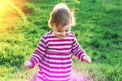 Счастливая маленькая прогулка девушки малыша outdoors на солнечный день Время весны, зеленая трава Стоковое Изображение RF