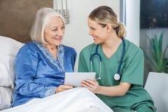 Счастливая медсестра и старшая женщина используя ПК таблетки Стоковое Изображение