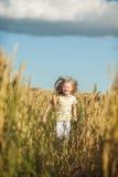 Счастливая милая девушка играя в пшеничном поле Стоковое фото RF