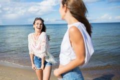 Счастливая милая женщина стоя на пляже смеясь над к ее другу Стоковое фото RF