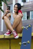 Счастливая милая женщина с скейтбордом в городе Стоковое Изображение RF