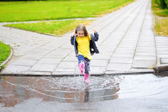 Счастливая милая маленькая девочка скача в лужицу после дождя в лете Стоковая Фотография
