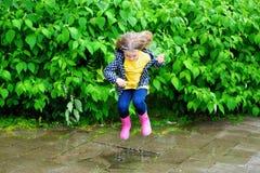 Счастливая милая маленькая девочка скача в лужицу после дождя в лете Стоковые Фотографии RF