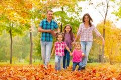 Счастливая милая семья в парке в октябре осени Стоковые Изображения RF