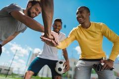 Счастливая многонациональная футбольная команда держа руки совместно перед игрой Стоковое Изображение