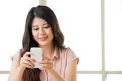 Счастливая молодая азиатская женщина используя умный обмен текстовыми сообщениями телефона Стоковая Фотография