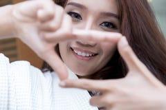 Счастливая молодая азиатская женщина показывая знак пальца рамки стоковые изображения rf