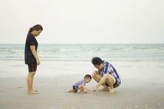 Счастливая молодая азиатская семья имея потеху на тропических каникулах o пляжа стоковая фотография