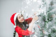Счастливая молодая азиатская хозяйственная сумка отверстия женщины около рождественской елки Стоковое фото RF