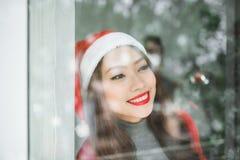 Счастливая молодая азиатская хозяйственная сумка отверстия женщины около рождественской елки Стоковые Фото