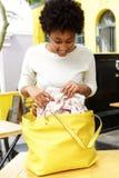 Счастливая молодая дама на кафе смотря что-то в ее сумке Стоковая Фотография