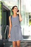 Счастливая молодая африканская женщина идя и говоря на мобильном телефоне Стоковая Фотография