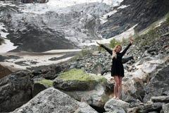 Счастливая молодая белокурая женщина в черном платье среди огромных камней на леднике Mestia стоковое изображение