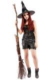 Счастливая молодая ведьма при веник, изолированный на белом backgro студии Стоковое фото RF