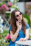Счастливая молодая городская женщина говоря smartphone и выпивая кофе в внешнем кафе Кавказский турист наслаждается ее европейцем Стоковые Фотографии RF