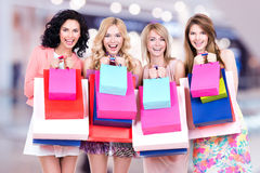 Счастливая молодая группа в составе женщины после ходить по магазинам в большом моле Стоковая Фотография RF