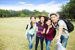 счастливая молодая группа делая selfie умным телефоном Стоковое Изображение RF