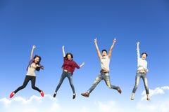 Счастливая молодая группа скача совместно Стоковые Фотографии RF