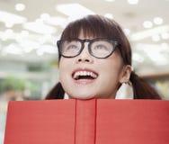 Счастливая молодая девушка школы в стеклах с открытой книгой стоковая фотография rf