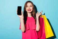 Счастливая молодая женщина брюнет держа мобильный телефон и хозяйственные сумки стоковая фотография rf