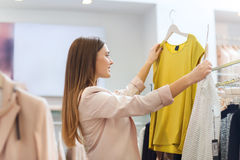 Счастливая молодая женщина выбирая одежды в моле Стоковая Фотография RF