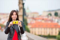 Счастливая молодая женщина в европейском городе на известном мосте Кавказские туристские принимают фото ее камерой в Праге Стоковое фото RF