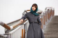 Счастливая молодая женщина в классическом пальто на шагах Стоковая Фотография RF