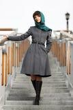 Счастливая молодая женщина в классическом пальто на шагах Стоковая Фотография
