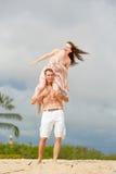 Счастливая молодая женщина в платье сидит на плечах парня Стоковое фото RF