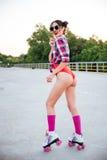 Счастливая молодая женщина в солнечных очках катаясь на коньках на коньках ролика outdoors Стоковые Изображения RF