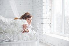Счастливая молодая женщина лежа на кровати Стоковые Изображения RF
