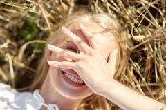Счастливая молодая женщина лежа на поле хлопьев Стоковое Фото