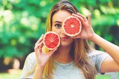 Счастливая молодая женщина держа грейпфрут Стоковое Изображение