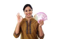 Счастливая молодая женщина держа индейца 2000 примечаний рупии и делая о'кеы Стоковое Фото