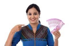 Счастливая молодая женщина держа индейца 2000 примечаний рупии Стоковое Фото