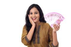 Счастливая молодая женщина держа индейца 2000 примечаний рупии Стоковое Изображение RF