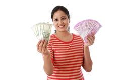 Счастливая молодая женщина держа индейца примечания 2000 и 500 рупий стоковое изображение