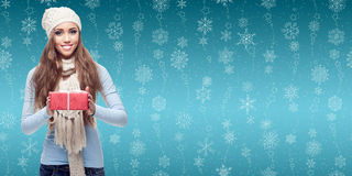 Счастливая молодая женщина держа подарок над предпосылкой зимы стоковое фото