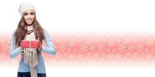 Счастливая молодая женщина держа подарок над предпосылкой зимы стоковая фотография