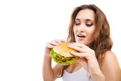 Счастливая молодая женщина есть большой yummy изолированный бургер Стоковые Изображения