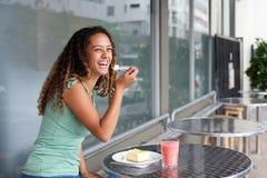 Счастливая молодая женщина есть торт на внешнем кафе Стоковые Изображения