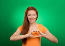 Счастливая молодая женщина делая знак сердца с руками Стоковая Фотография