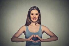 Счастливая молодая женщина делая знак сердца с руками Стоковые Фотографии RF