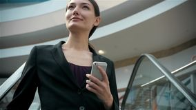 Счастливая молодая женщина используя умный телефон в торговом центре Фрилансер коммерсантки с smartphone в крупном аэропорте акции видеоматериалы