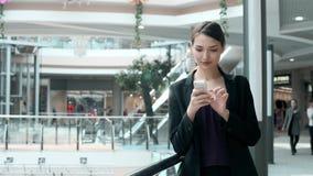 Счастливая молодая женщина используя умный телефон в торговом центре Фрилансер коммерсантки с smartphone в крупном аэропорте Стоковые Фото