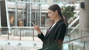 Счастливая молодая женщина используя умный телефон в торговом центре Фрилансер коммерсантки с smartphone в крупном аэропорте Стоковые Фотографии RF