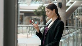 Счастливая молодая женщина используя умный телефон в торговом центре Фрилансер коммерсантки с smartphone в крупном аэропорте Стоковые Изображения
