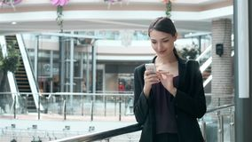 Счастливая молодая женщина используя умный телефон в торговом центре Фрилансер коммерсантки с smartphone в крупном аэропорте Стоковая Фотография RF