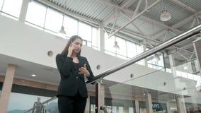 Счастливая молодая женщина используя умный телефон в торговом центре Фрилансер коммерсантки с smartphone в крупном аэропорте Стоковое Изображение RF